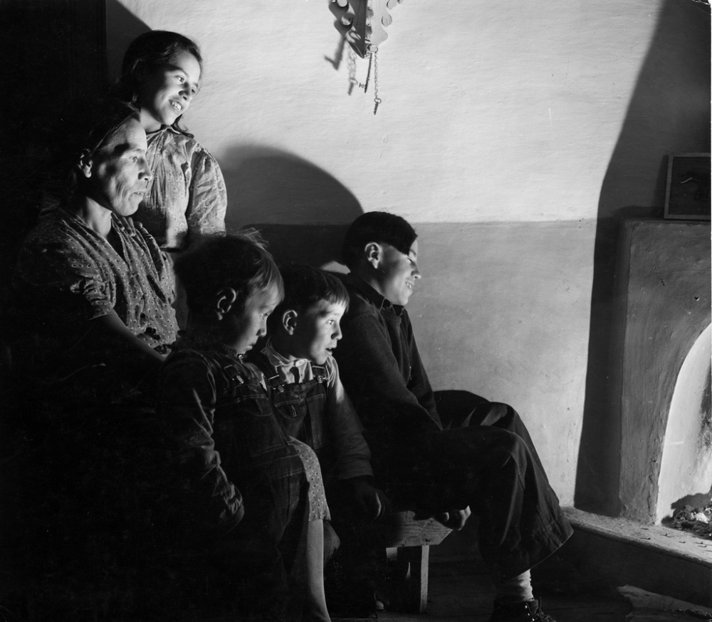 A family in front of their kiva fireplace, Trampas, New Mexico, 1943